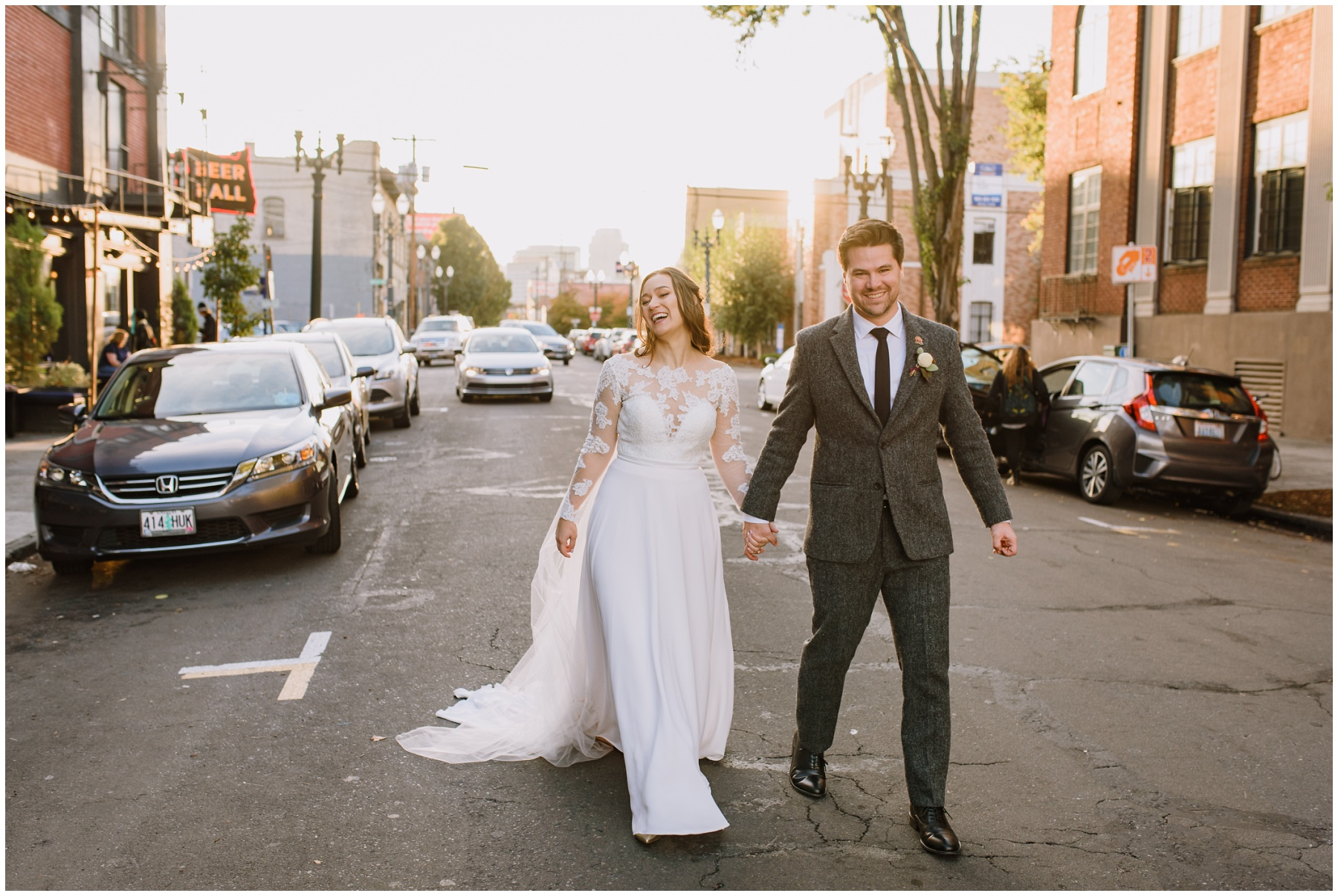 A bride and groom walking in the street at sunset outside the Evergreen Portland
